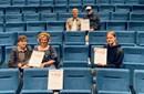 Fem ungdomar sitter i en biosalong med blå stolar. De håller upp sina diplom.