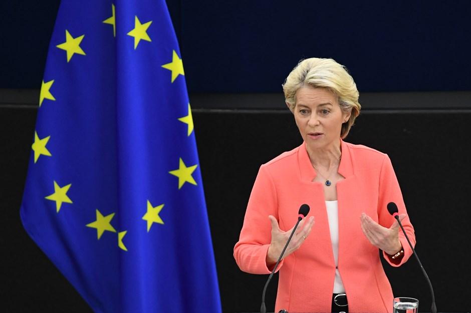 En kvinna (Ursula von der Leyen) talar engagerat i en talarstol. Bredvid henne syns en EU-flagga.