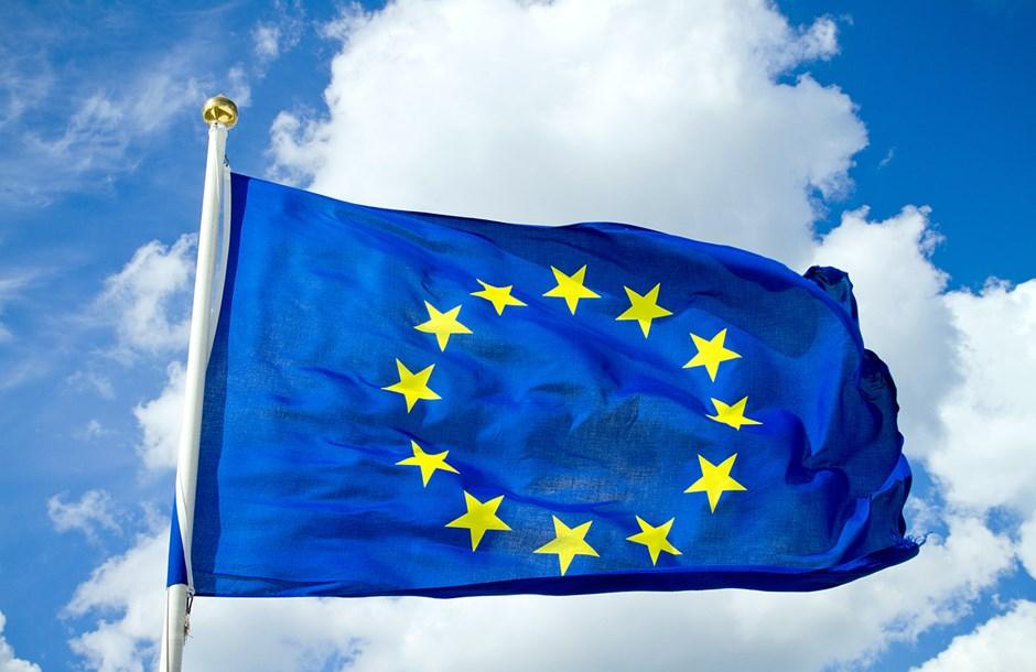 En blå EU-flagga med gula stjärnor vajar i vinden. Bakgrund: en blå himmel med vita moln.