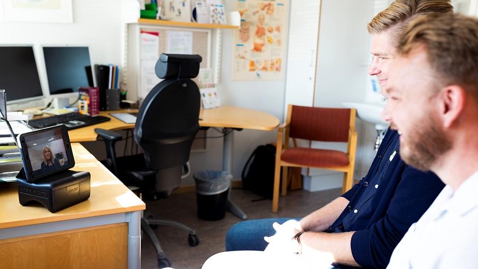 Två män sitter framför ett digitalt möte på en ipad.