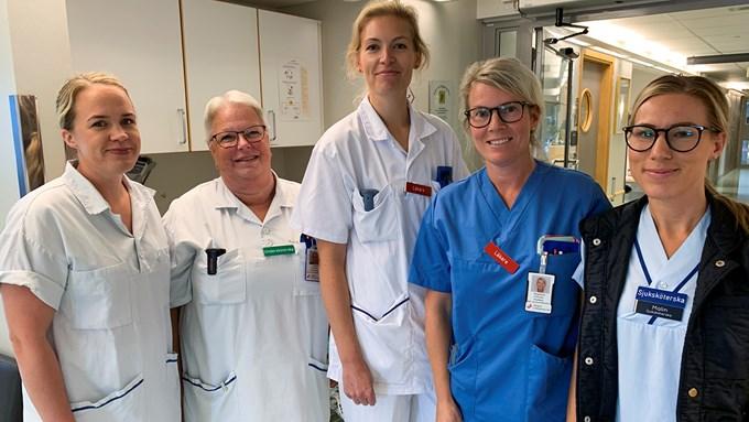 Fem kvinnor i vårdkläder står i grupp