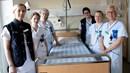 Sex vårdklädda kvinnor står runt en sjukhussäng